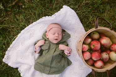 a baby lays sleeping next to a basket of apples