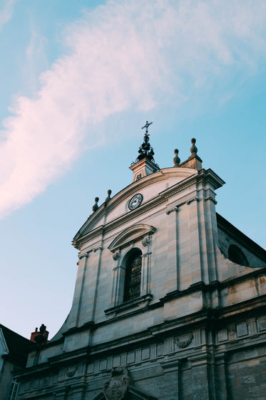 a baroque church points a crucifix at the blue sky