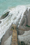 a bird's eye view of wooden steps to the foaming sea below