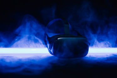a black headset surrounded by fog in blue light
