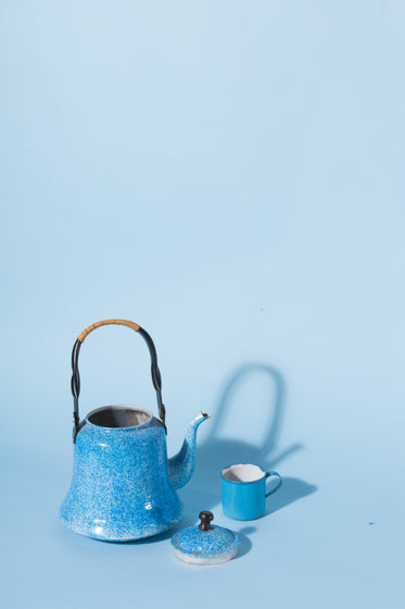 a blue kettle and mug against a blue background