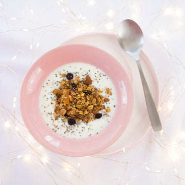 a bowl of muesli in a pink bowl on a saucer with spoon