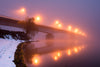 a bridge with yellow lights blurred by thick fog