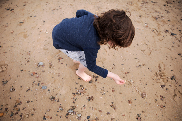 A Child With Long Brown Hair Inspects Pebbles On the Beach