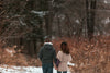a close up of a couple strolling through winter