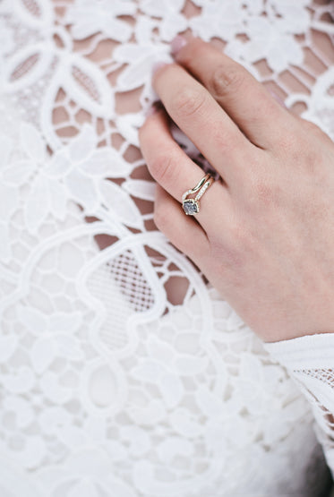 a close up of the brides wedding ring and band