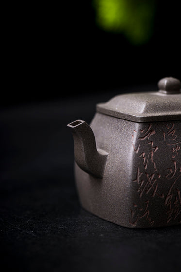 a close up view of a grey teapot with a square spout