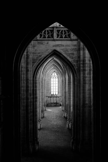 a corridor of archways leads to a gothic window