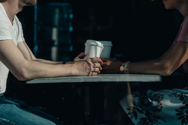 a couple chat over coffee cups on a sunny day in a cafe