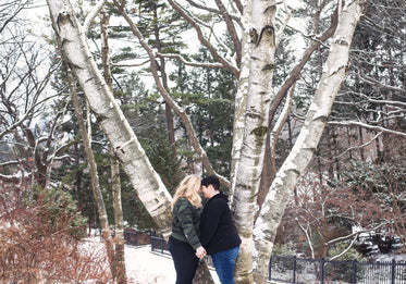 a couple share a moment under snow covered trees
