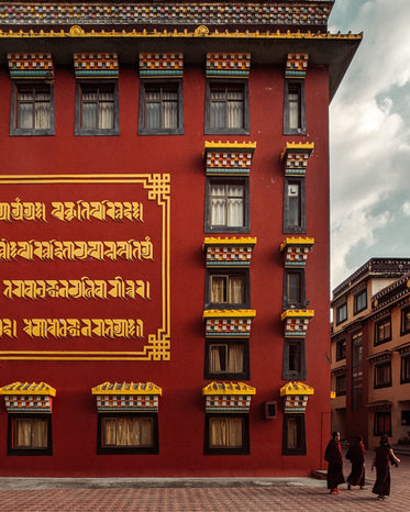 a crimson building with gold writing on the walls