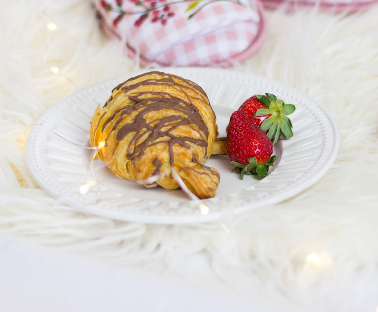 A Croissant Laced With Chocolate On A White Paper Plate