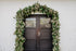 a dark wooden doorway framed by a trellis of greenery