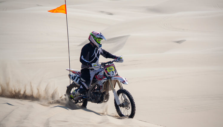 A Dirt Bike Racer Spins Sand Riding Over Dunes