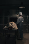 a doctor in scrubs puts a corpse into a mortuary freezer