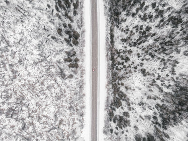 a drone view of a red pickup truck on a road surrounded by forest