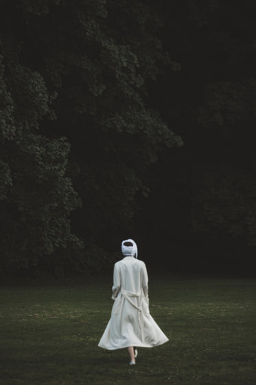 a figure in white gauze walks towards the woods