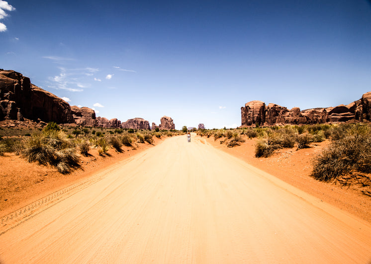 A Figure Stands On A Road In The Desert under Blue Skies