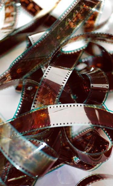 a film reel lays tangled against a white background