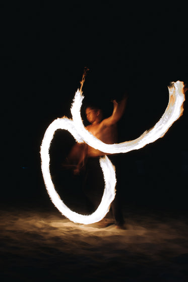 a fire dancer cuts figures of eight at night on a beach