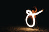 a fire dancer draws shapes on a beach at night