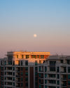 a full moon over buildings