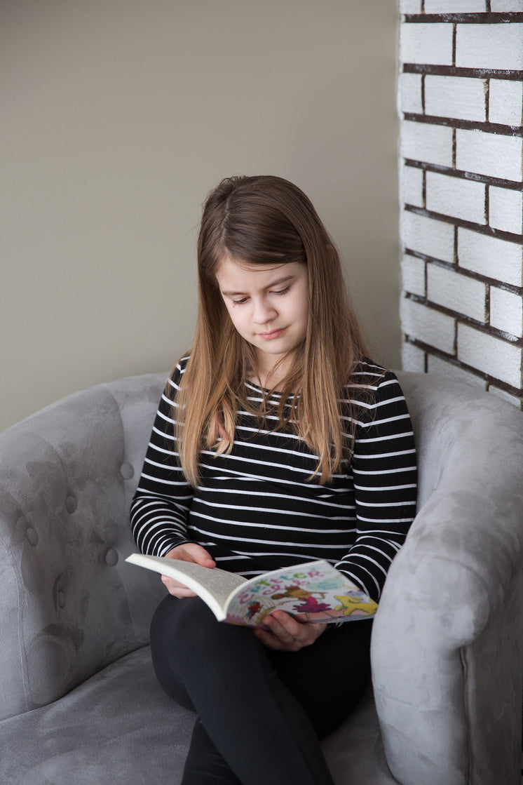 A Girl Sitting In A Chair Reads A Book