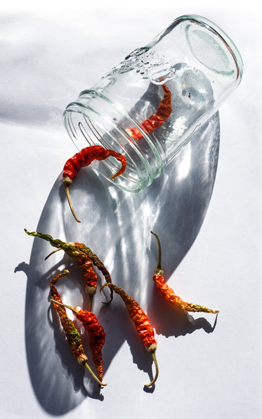 a glass jar with red chili peppers falling out of it