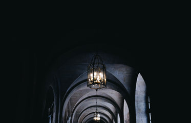 a glass lantern of candles in a corridor of arches