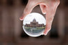 a grand building refracted through a glass orb