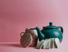 a green teapot and teabags leaning on it