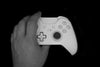 a hand grabbing a gaming controller against a black background