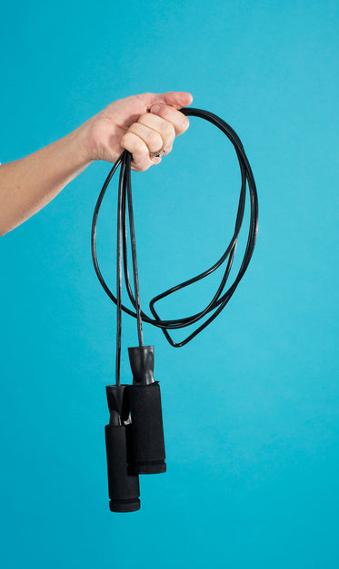 a hand grips a black gathered jump rope