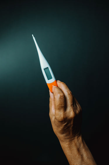 a hand holds up a thermometer against black background