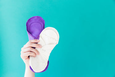 a hand holds up two reusable menstrual pads