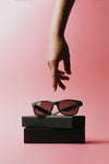 a hand reaches for black sunglasses sitting on a case