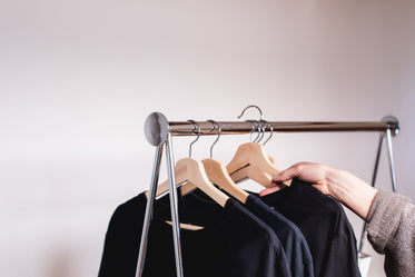 a hand removes a sweater from a clothing rack