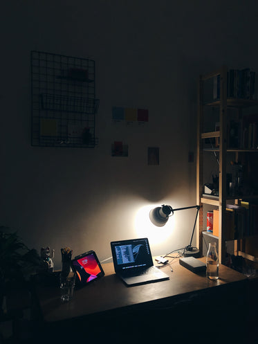 a laptop and tablet beam from a desktop backlit by a lamp