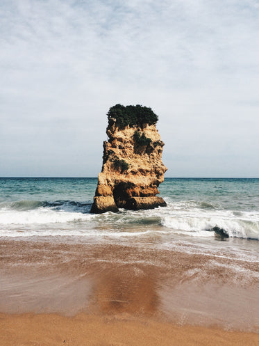 a large rock stands guard in the middle of the ocean