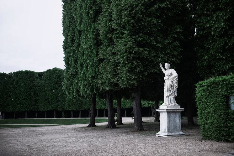 A Large Statue Sits In A Grove Of Trees