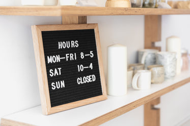 a letter board displays opening times on a shop shelf