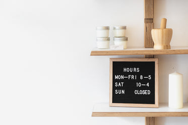 a letterboard on a busy shop shelf denotes opening times