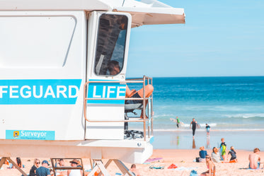 a lifeguard sits in raised white stand