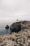 a lighthouse watches over a rocky coastline