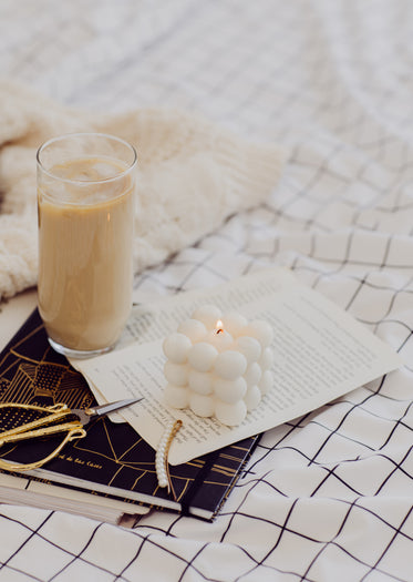 a lit candle with iced coffee and hair accessories