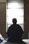 a male patient on a hospital bed silhouetted by window light