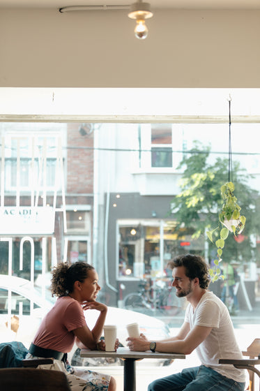 a man and a woman are framed against a sunny window