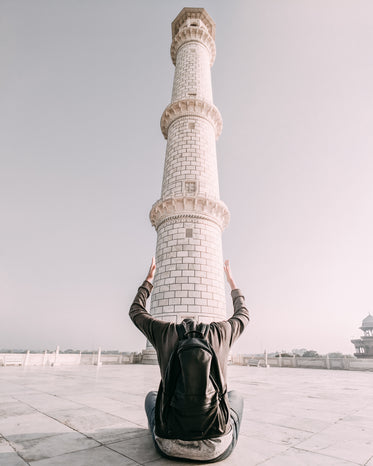 a man frames the base of a tower with his arms