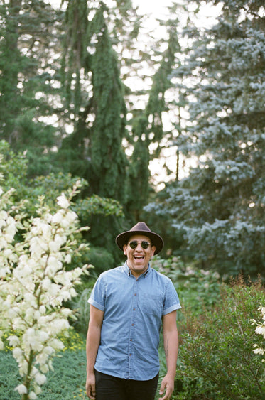 a man in a fedora and sunglasses beams in the woods