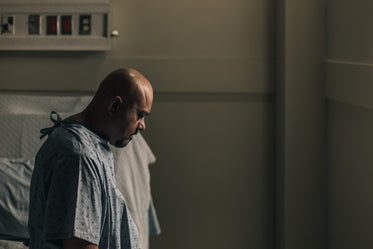 a man in a hospital room stares down at the floor
